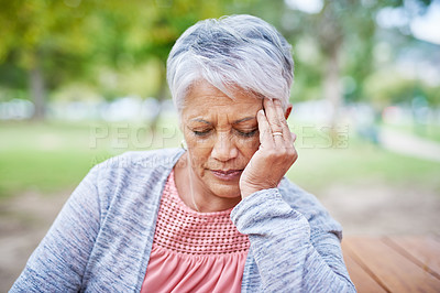 Buy stock photo Cropped shot of a retired senior woman suffering from a headache while sitting alone in the park during the day