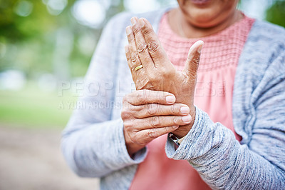 Buy stock photo Cropped shot of an unrecognizable senior woman suffering from arthritis in her hand while in the park alone