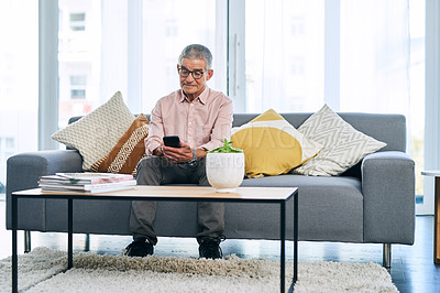 Buy stock photo Full length shot of a retired senior man using his cellphone while sitting on the sofa in the living room