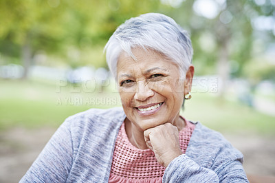Buy stock photo Cropped portrait of a retired senior woman sitting alone and smiling while in the park during the day