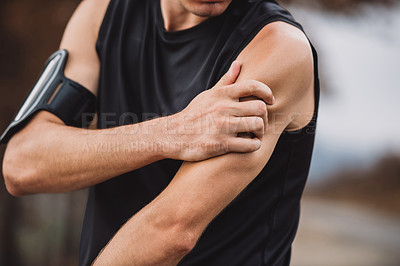 Buy stock photo Closeup shot of an unrecognizable young man suffering from a sports injury while exercising outdoors