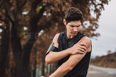 Buy stock photo Shot of a sporty young man suffering from a sports injury while exercising outdoors