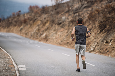 Buy stock photo Rearview shot of a sporty young man running outdoors