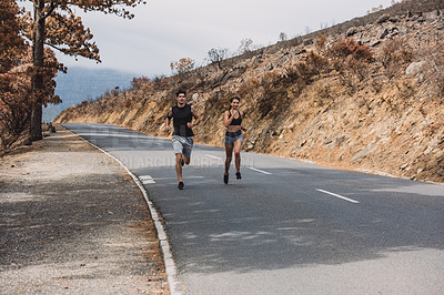 Buy stock photo Shot of a sporty young couple running together outdoors