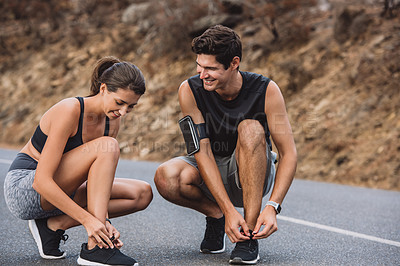 Buy stock photo Shot of a sporty young couple tying their laces while exercising outdoors