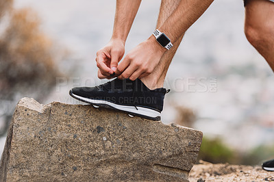 Buy stock photo Closeup shot of an unrecognizable man tying his laces while exercising outdoors