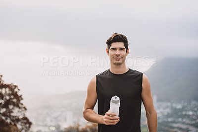 Buy stock photo Portrait of a sporty young man holding a bottle of water while exercising outdoors