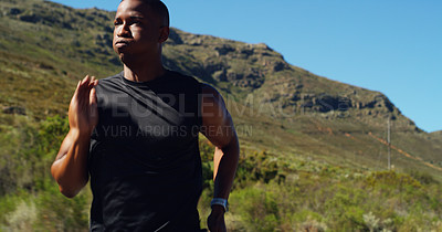 Buy stock photo Shot of a sporty young man running outdoors against a mountain background