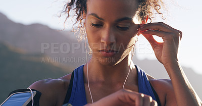 Buy stock photo Cropped shot of a young woman inserting her earphones while out for a run