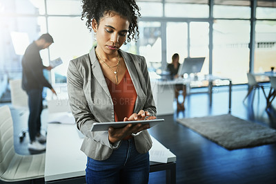 Buy stock photo Shot of an attractive young businesswoman using a digital tablet at work with colleagues in the background