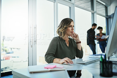 Buy stock photo Shot of an attractive young businesswoman working on a computer in an office with colleagues in the background