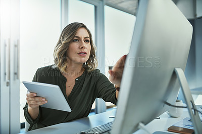 Buy stock photo Shot of an attractive young businesswoman using a computer and digital tablet in her office