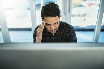 Buy stock photo Shot of a young businessman suffering from a headache while working on a computer in his office