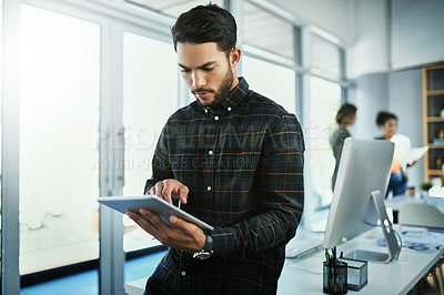 Buy stock photo Shot of a handsome young businessman using a digital tablet in a office with colleagues in the background