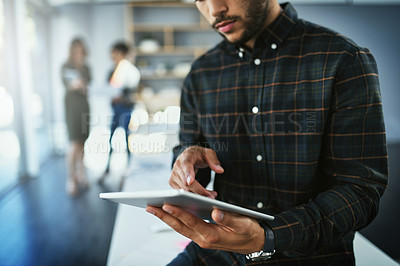 Buy stock photo Shot of an unrecognizable businessman using a digital tablet in a office with colleagues in the background