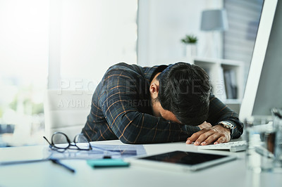 Buy stock photo Shot of a young businessman sleeping at his office desk at work