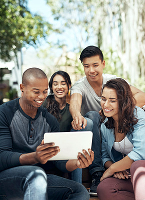 Buy stock photo Shot of a group of young men and women using a digital tablet together on campus