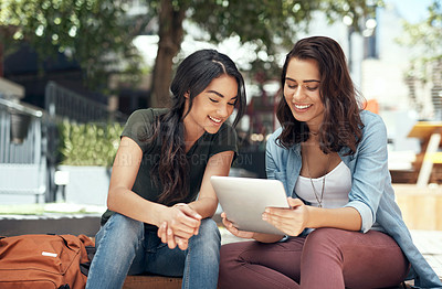 Buy stock photo Shot of two young women using a digital tablet together on campus