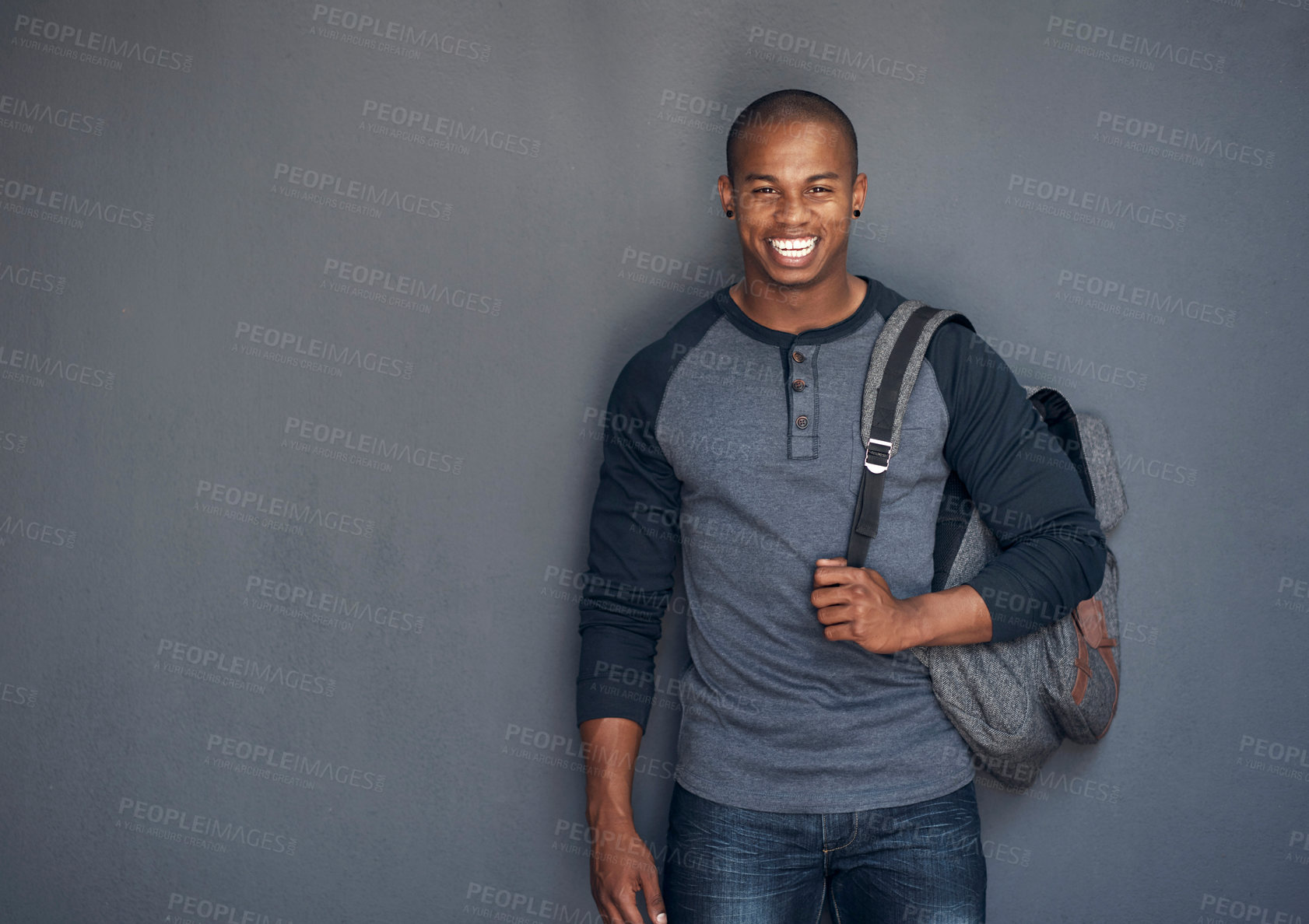 Buy stock photo Studio portrait of a young man carrying a schoolbag against a grey background