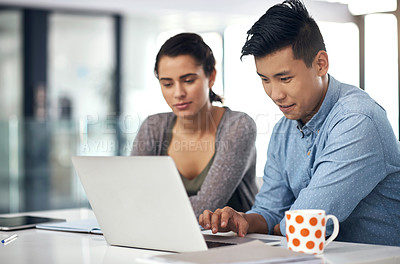 Buy stock photo Shot of a young man and woman using a laptop while studying together at college