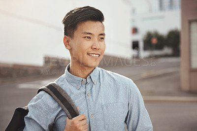 Buy stock photo Shot of a confident young man walking to college through the city