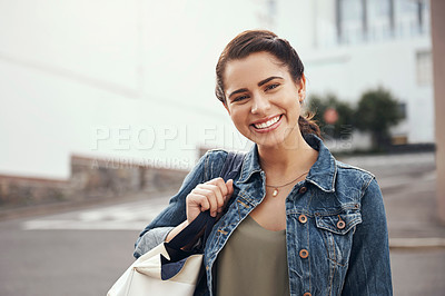 Buy stock photo Shot of a happy young woman carrying a schoolbag in the city