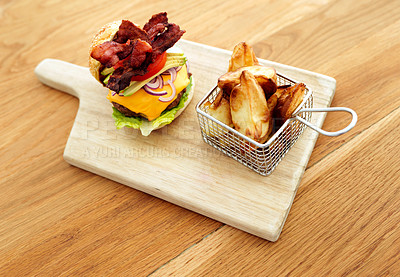 Buy stock photo Shot of a delicious burger and fried potato chips on a cutting board in the kitchen during the day