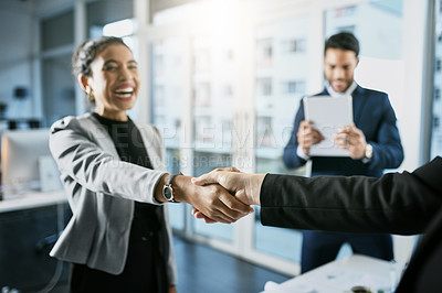 Buy stock photo Cropped shot of three unrecognizable businesspeople agreeing with a handshake while in their office during the day