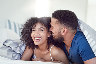 Buy stock photo Cropped shot of an affectionate young couple laughing together while relaxing under their blankets at home