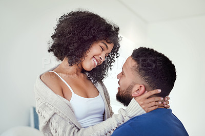 Buy stock photo Cropped shot of an affectionate young woman smiling while embracing her husband in their bedroom at home