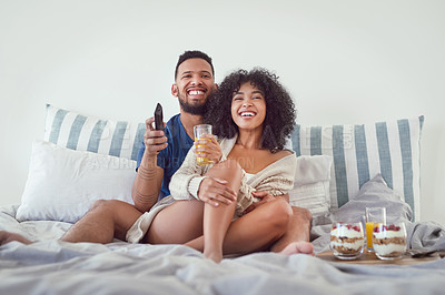 Buy stock photo Full length shot of an affectionate young couple enjoying watching tv while relaxing on their bed at home