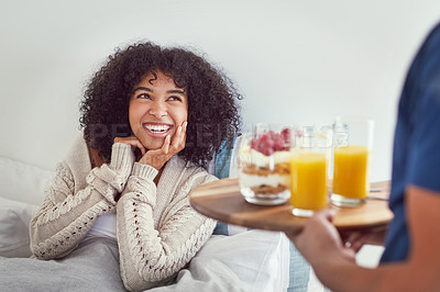 Buy stock photo Cropped shot of an attractive young woman smiling as her husband serves her breakfast in bed at home