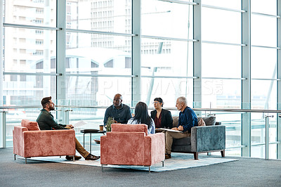 Buy stock photo Full length shot of a group of business colleagues talking while sitting in their office