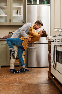 Buy stock photo Full length shot of an affectionate young couple dancing together in their kitchen at come