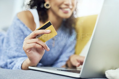 Buy stock photo Cropped shot of a young woman holding her credit card while using her laptop