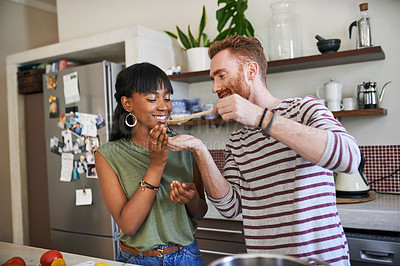 Buy stock photo Shot of a man letting his girlfriend taste his food from a wooden spoon
