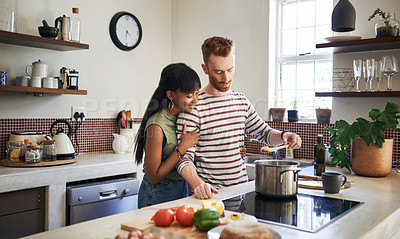 Buy stock photo Shot of a young man cooking while his girlfriend embraces him from behind