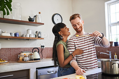 Buy stock photo Shot of a young man having his girlfriend taste his food while cooking