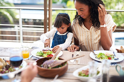 Buy stock photo Shot of an adorable little girl and her mother enjoying themselves during a meal with family outdoors
