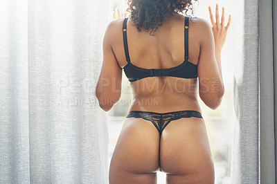 Buy stock photo Rearview shot of an unrecognizable young woman looking outside her bedroom window while wearing lingerie