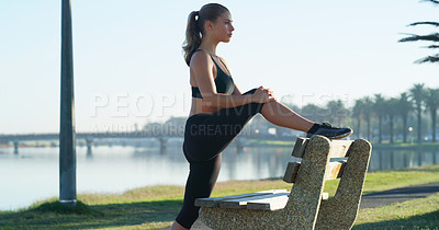 Buy stock photo Shot of a young woman stretching against a park bench
