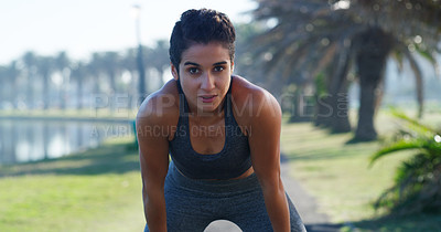 Buy stock photo Cropped shot of a young woman standing with her hands on her knees while out running