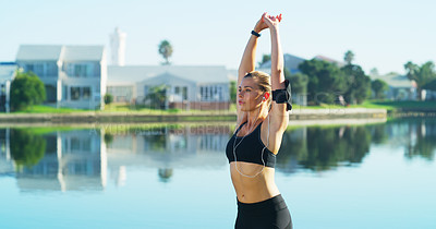 Buy stock photo Cropped shot of a sporty young woman stretching before her run