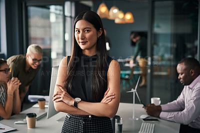 Buy stock photo Cropped portrait of an attractive young businesswoman standing in her office while her colleagues work behind her during the day