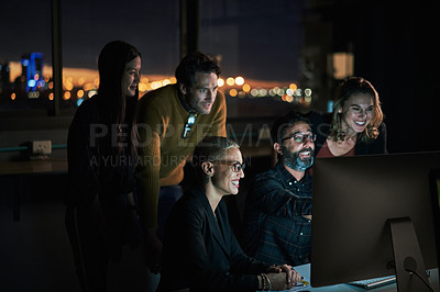 Buy stock photo Cropped shot of a diverse group of businesspeople working over a computer while in the office late at night