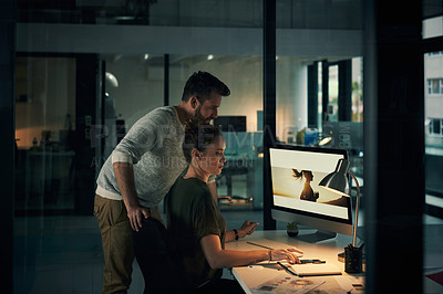 Buy stock photo Shot of two young coworkers using a computer during a late night at work