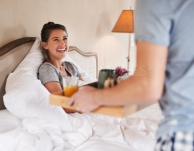 Buy stock photo Shot of a beautiful young woman looking happy while being served breakfast in bed by her boyfriend at home