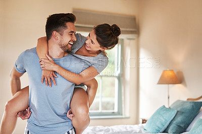 Buy stock photo Shot of a playful young couple spending some quality time together in their bedroom