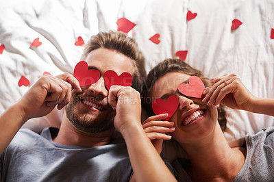 Buy stock photo Shot of an affectionate young couple covering their eyes with heart shapes in the bedroom at home