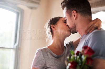 Buy stock photo Shot of a young man surprising his girlfriend with a bunch of roses in their bedroom at home